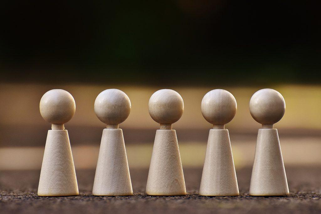 fünf Holzfiguren in einer Reihe symbolisieren Teamcoaching